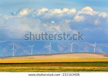 Detail of windmills on wind-farm wind farm with mountains and clouds