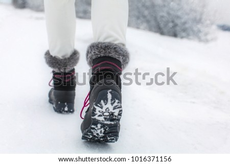 Detail of woman lifting her black and gray snow boot with faux fur and purple laces, showing tread of the boots, shot on winter overcast day. #1016371156