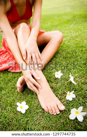 Detail of woman's bare feet on grass covered in frangipani flowers