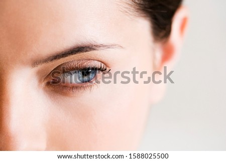 Detail of woman's face showing left eye with blue iris