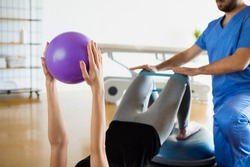 Detail of woman's hands holding purple fitness ball during recovery session in a medical center or loft studio, while physiotherapist assist the rehabilitation exercises with rubber band.