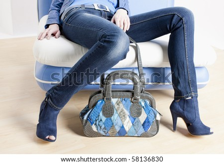 detail of woman wearing blue shoes and with handbag