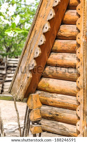 Detail of wooden beams in the wall of the round log home built on old technology as a creative element to natural background