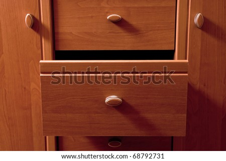 Detail of wooden chest of drawers. With shadows