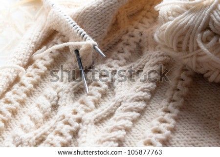 Detail of woven handicraft knit woolen design texture and knitting needle. Fabric beige background