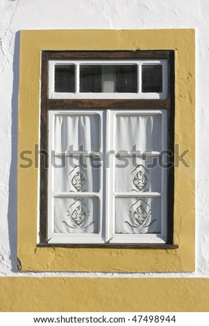 Detail of yellow window on a old house at algarve, south of Portugal