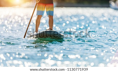 Detail of young man standing on paddleboard. Paddleboarding is the modern way of transportation and water activity sport.