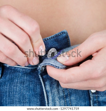 Detail of young woman fastening button on denim jeans