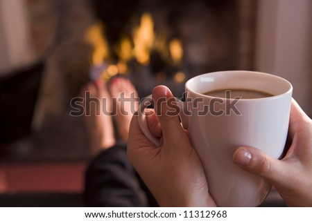 Detail of young woman holding cup of coffee by fire