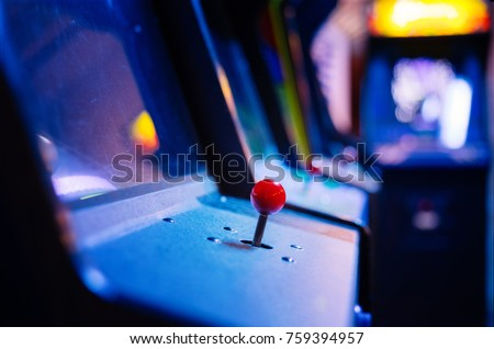 Detail on a red joystick of an old vintage arcade video game with more machines in the background