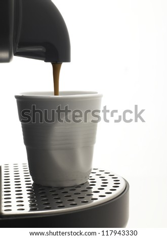 Detail on a white background a coffee machine with fake plastic cup