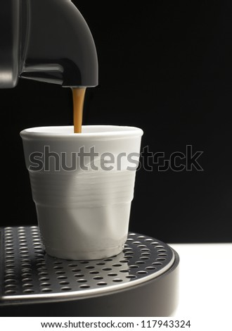 Detail on black background a coffee machine with fake cup
