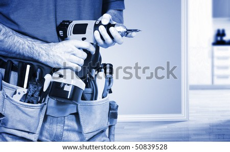detail on handyman manual worker, toolsbelt and  drill in his hands