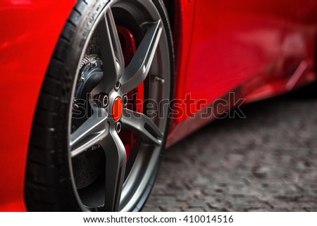 Detail on hot red super-sport car wheels with sport breaks #410014516
