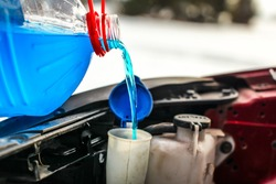 Detail on pouring antifreeze liquid screen wash into dirty car from blue and red anti freeze water container.