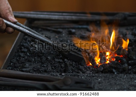 detail photo of a blacksmith who stirs the fire