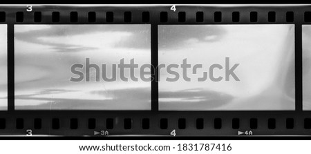 detail scan of 35mm filmstrip with the frame edge numbers 3 and 4, grungy looking film material with empty frames or cells and nice light reflection. Stok fotoğraf ©