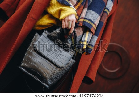 detail shot. attractive woman outdoors posing in a checked patternedscarf and brown coat, wearing a golden ring and watch and holding a black leather croc effect backpack. fashion outfit, streetstyle