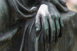 Detail shot of a female hand of a bronze statue of a woman in a park, Germany