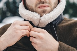 Detail shot of a man buttoning up his winter coat