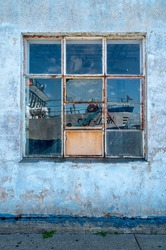 Detail shot of a window of a port warehouse with blue sky and boat reflecting in its square tiled window.  Cracked and peeled white, blue and red wall. Old building decay.