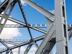 Detail shot of an historic gray painted Dutch riveted truss bridge against a blue sky.
