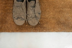 Detail shot of dirty dried muddy and messy sneaker shoes totally covered with mud looking unrecognizable while laying on a brown coco doormat