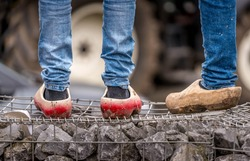 Detail shot of farmers legs in clogs and jeans during protests in The Hague