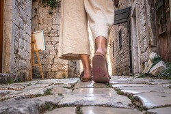 Detail shot of female legs wearing comfortable travel sandals walking on old medieval cobblestones street dring sightseeing city tour. Travel, tourism, and adventure concept.