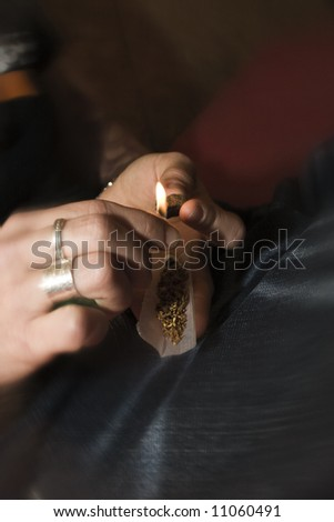 detail shot of human hands preparing a marijuana cigaret in a party