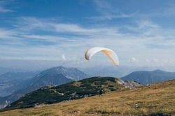Detail to break up parachute and gather necessary pressure and wind into his parachute so he can soar into clouds and enjoy flight over Krippenstein Mountain overlooking Dachstein and Hallstattsee.