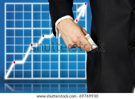 Detail view of a business man putting money into pocket