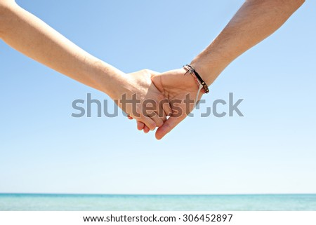 Detail view of a man and a woman hands being held together against a blue sky and sea, on a sunny summer holiday break, outdoors. Tourists holding hands, lifestyle. Honeymoon romance on beach.