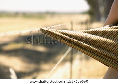 Detail view of a piece of fabric caught on a barbed wire fence