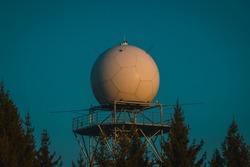 Detail view of a rain radar or meteorological doppler radar for measuring precipitation in early morning hours during sunrise on Pasja Ravan hill in Slovenia