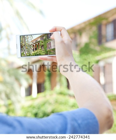 Detail view of a young woman hand holding a smartphone device up and taking photos of a monument visiting a destination city on holiday. Vacation travel technology lifestyle networking. #242774341