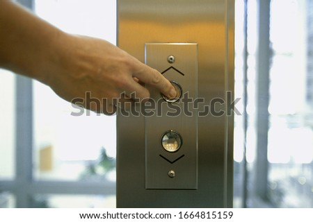 Detail view of hand pushing elevator button