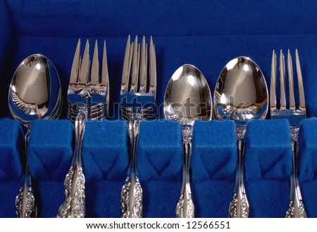 Detail view of silverware in a storage chest.