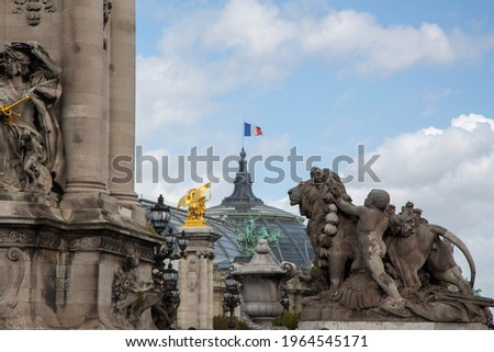 Detail view of the Alexandre III bridge and the national french flag waving on the Grand Palais rooftop in Paris, France. Stock photo ©