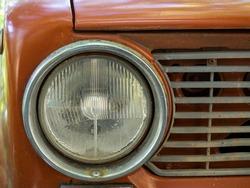 Detail view of the headlight. Retro Soviet car. Front light. Retro automobile scene. Circle headlamp.