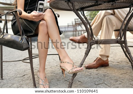 Detail view of two business people's legs under a coffee table while in a meeting outdoors, using a cell phone.