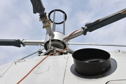 Detail view on main rotor blades and rotor mast of the white twin-engine multi mission or multipurpose Helicopter.