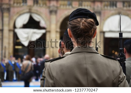 Detail with uniformed women standing during the military ceremony in Bologna, Italy. In the foreground, a woman seen from behind with a bayonet rifle.
