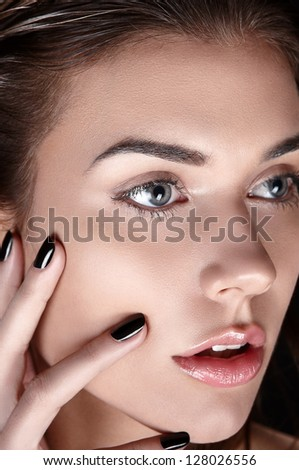 Detailed beauty shot of young woman. Pure healthy shiny skin, perfect black nails manicure, natural looking makeup, clean. Touching her face with hands. Close up.