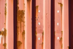 Detailed close up of red metal made container covered with rust. Grunge background.