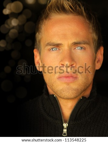 Detailed close up portrait of a young blond man with beautiful blue eyes