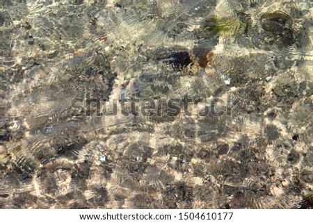 Detailed close up view on water surfaces with wave and ripples and the sunlight reflecting at the surface
