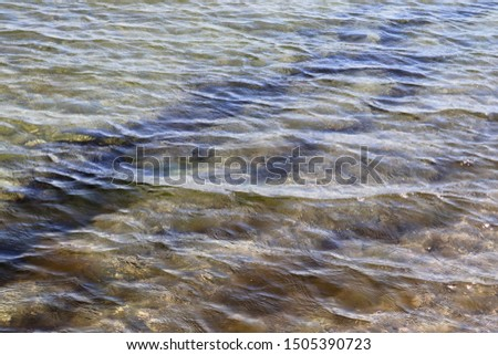 Detailed close up view on water surfaces with wave and ripples and the sunlight reflecting at the surface #1505390723