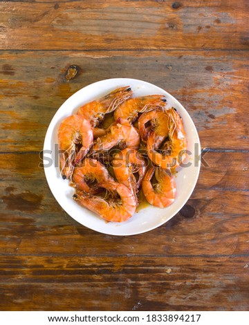 Detailed Closeup of Garlic Shrimps bathed in Chili Sauce, on a white plate on a wood table. A variation of Gambas al Ajillo. Foto d'archivio ©