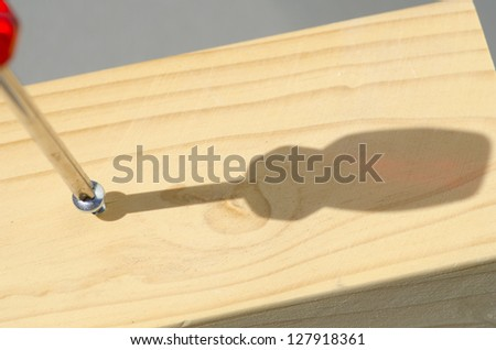 Detailed closeup of screwdriver and screw in timber panel outdoor with shadow and blurred background and copy space.